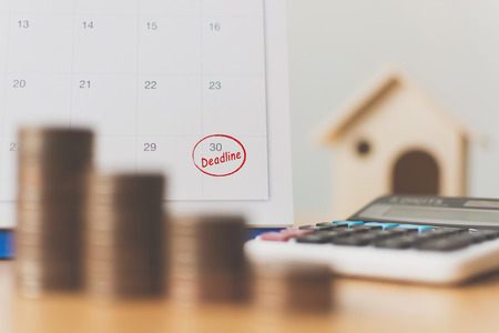 Tax payment season and finance debt collection deadline concept. Money coins stack, calendar, calculator and wooden house Stockfoto