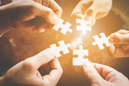 Hand of diverse people connecting jigsaw puzzle. Concept of partnership and teamwork in business 写真素材