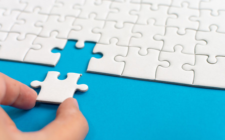 Hand putting piece of white jigsaw puzzle on blue background. Team business success partnership or teamwork.