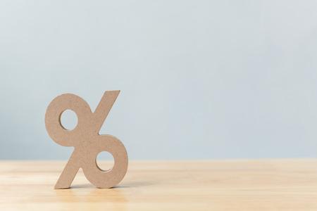 Icono de símbolo de signo de porcentaje de madera sobre mesa de madera con fondo blanco.