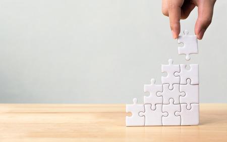 Organiser à la main l'empilement des puzzles comme marches d'escalier sur une table en bois. Concept d'entreprise pour le processus de réussite de la croissance