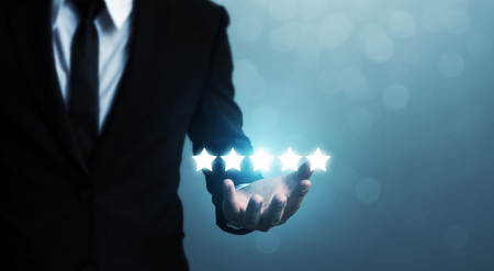 Businessman hand holding five star symbol to increase rating of company concept