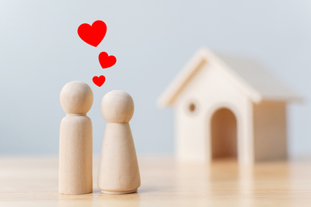 Wood doll couple lover with house. Family home, Insurance and property investment real estate concept Stock Photo