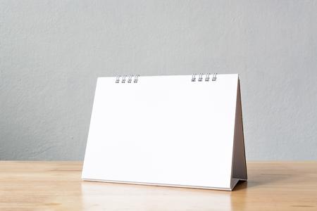 Calendario de escritorio en blanco de la maqueta en la mesa de madera. Plantilla para el diseño