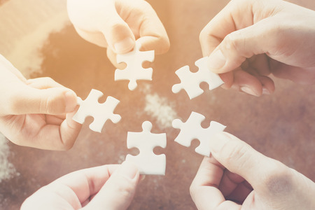 Hand of diverse people connecting jigsaw puzzle. Concept of partnership and teamwork in business Stockfoto