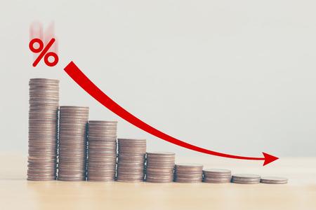 Grafico di riduzione della pila di monete con freccia rossa e icona percentuale, concetto di gestione dei tassi di interesse finanziari e di gestione del business di gestione del rischio Archivio Fotografico