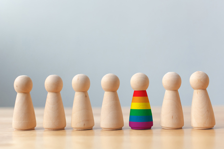 Human rights of LGBT campaign concept. Wooden dolls with rainbow colors are different stand out from crowd