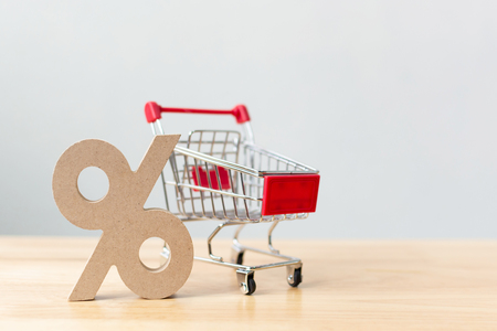 Percentage sign symbol icon wooden and shopping cart on wood table with white background