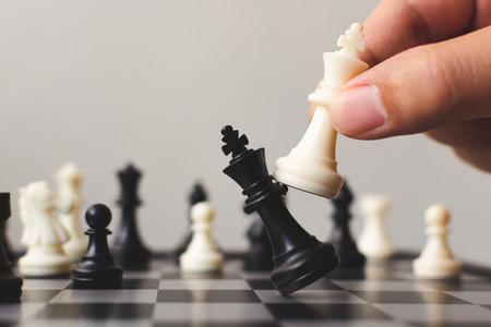 Pianifica la strategia principale del concetto di leader della competizione aziendale di successo, la mano del gioco da tavolo del giocatore che mette il pedone bianco, copia spazio per il tuo testo Archivio Fotografico