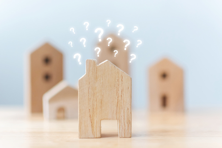 Real estate developer and managing property investment concept. Selective focus wooden houses with question mark on table Stockfoto