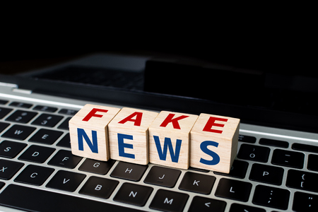 Wooden block cube shape with word FAKE NEWS on laptop