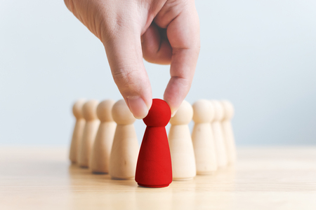 Human resource, Talent management, Recruitment employee, Successful business team leader concept. Hand chooses a wooden people standing out from the crowd.
