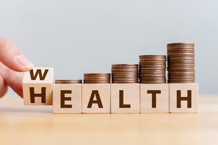 Ręcznie przerzuć drewnianą kostkę ze słowem bogactwo do zdrowia ze stosem monet przyspiesz rosnącą wartość wzrostu. Inwestycja w koncepcję ubezpieczeń na życie i opieki zdrowotnej