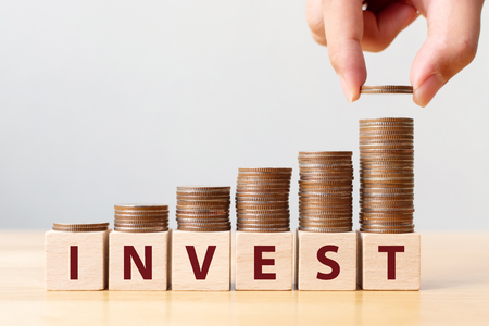 Hand putting coins on stack stair as step growing growth and wooden cube block with word INVEST. Investment and save money concept