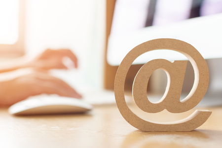 Email marketing concept, Hand using computer sending message with wooden email address symbol Фото со стока