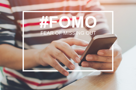 FOMO, fear of missing out concept. Close-up image of male hands using mobile smartphone Фото со стока