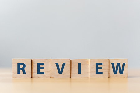 The word REVIEW on wooden cube block on wood table Фото со стока