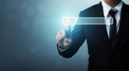 Searching information data on internet networking concept. Hand of businessman touching magnifying glass icon search
