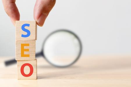 Concetto di ottimizzazione dei motori di ricerca. Mettere a mano la forma del cubo del blocco di legno con la parola SEO e la lente d'ingrandimento Archivio Fotografico