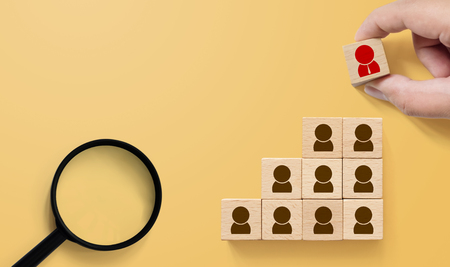 Human resource and talent management and recruitment business concept, Hand putting wood cube block on top staircase and magnifying glass on yellow background Фото со стока