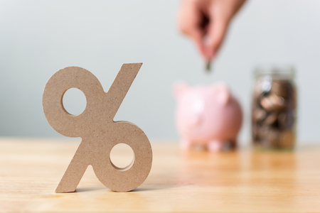Percentage sign symbol with blurred hand putting money coin in piggy bank