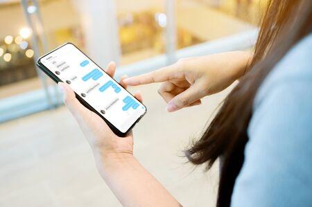 Mujer que usa su teléfono inteligente móvil. Ella charlando con un amigo en el teléfono móvil