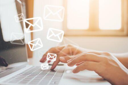 E-mailmarketing en nieuwsbriefconcept. Hand van de mens die bericht en laptop met e-mailpictogram verzendt