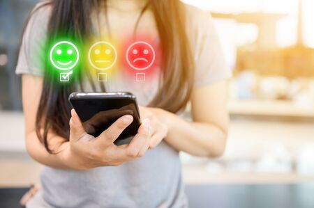 Customer service experience and business satisfaction survey. Close-up image of female hands using mobile smartphone choose face smile