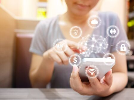 Young woman smiling and using smartphone with icon technology artificial intelligence (AI) and internet of things (IOT)