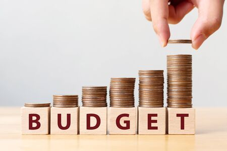 Hand putting coins on stack stair as step growing growth and wooden cube block with word BUDGET. Money annual budget concept