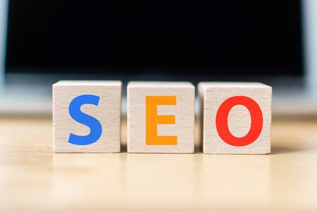 Search engine optimization concept. Wooden block cube shape with word SEO and laptop Фото со стока