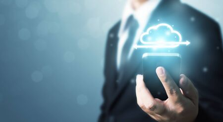 Cloud computing and technology network connection concept. Businessman hand holding mobile smart phone cloud server tranfer data device