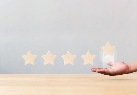 Hand holding wooden five star shape on table. The best excellent business services rating customer experience concept Stock Photo