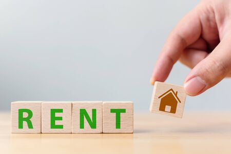 Hand holding wood cube block with icon house and word RENT. Property investment and house mortgage financial concept