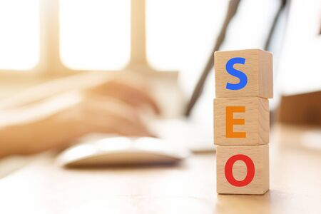 Search engine optimization concept. Hand using laptop with wood block cube shape with word SEO Stock Photo