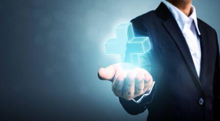 Main d'homme d'affaires tenant un signe plus virtuel signifie offrir des choses positives (comme des avantages, un développement personnel, un réseau social) Banque d'images