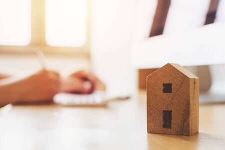 Close up wooden toy house with hand signing loan document to home ownership. Mortgage and real estate property investment