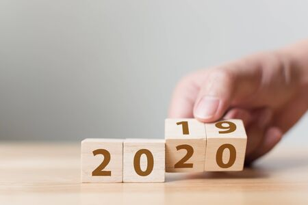 New year 2019 change to 2020 concept. Hand flip over wood cube block Stock Photo