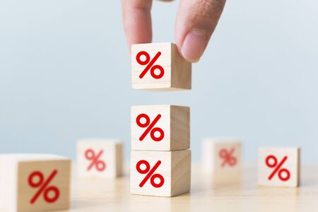 Interest rate financial and mortgage rates concept. Hand putting wood cube block increasing on top with icon percentage symbol upward direction Stock Photo