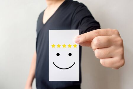 Customer service experience and business satisfaction survey. Man holding card with smiley face with five star Stock Photo