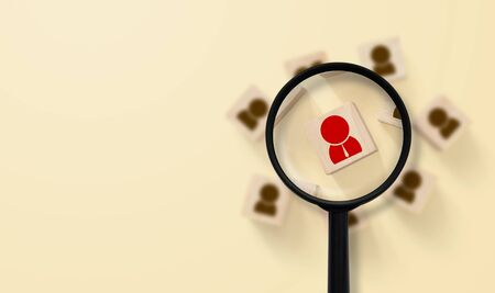Human resources management and recruitment concept. Magnifying glass is searching for the human icon on top Stock Photo