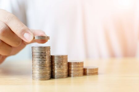 Concept save money financial business investment. Hand of male putting coins stack step growing growth value