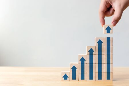 Ladder career path for business growth success process concept.Hand arranging wood block stacking as step stair with arrow up Stock Photo