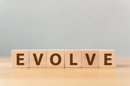 The word EVOLVE on wooden cube block on wood table Stock Photo