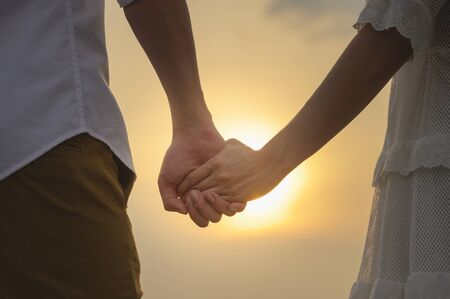 Young couples hold hands in the evening and look at the sunset