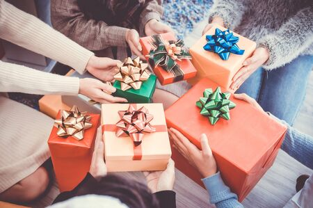 Asian people party celebrate christmas and new year eve in house. Man and woman giving gift box together