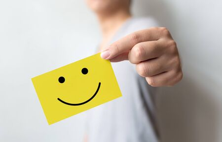Customer service experience and business satisfaction survey. Man holding yellow card with smiley face