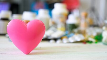 Pink heart icon and pill and tablet medicine on wood table. Concept healthcare medical, Insurance for your health