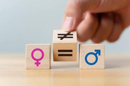 Concetti di uguaglianza di genere. Capovolgere a mano il cubo di legno con il simbolo cambiamento disuguale in segno uguale Archivio Fotografico