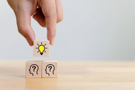 Concept creative idea and innovation. Hand choose a wooden cube block with light bulb and head human symbol icon
